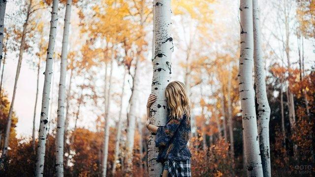 Светловолосая девушка обнимает ствол берёзы в осеннем лесу