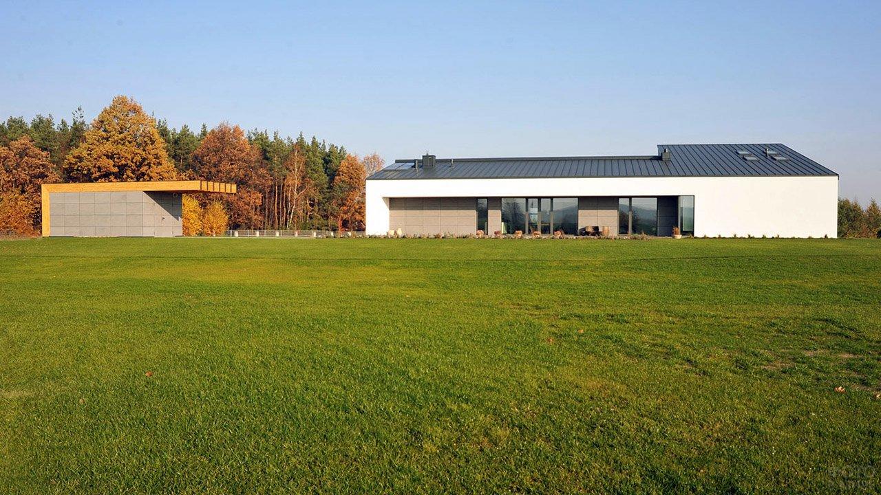 Белый загородный дом с чёрной односкатной крышей и просторной зелёной лужайкой