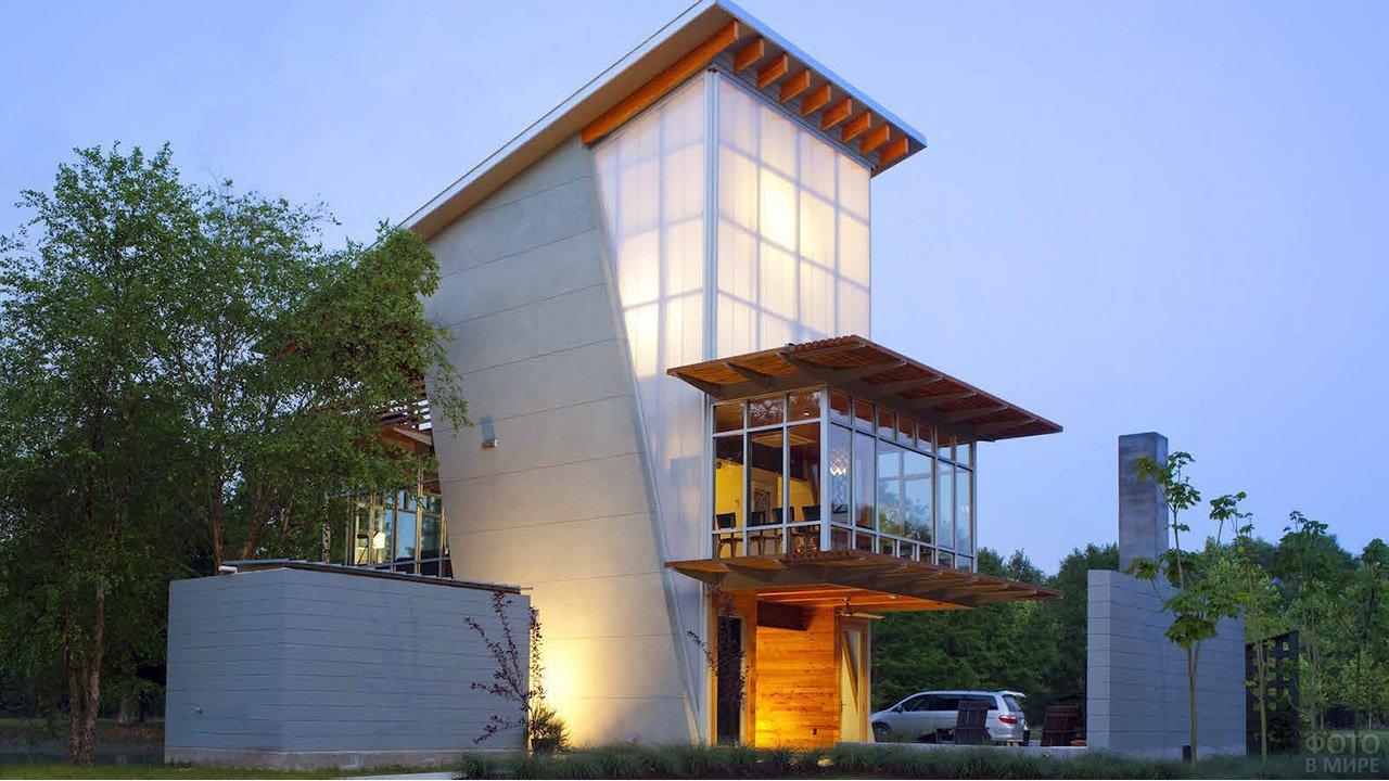 Дизайнерский особняк с односкатной крышей с большим свесом над балконом