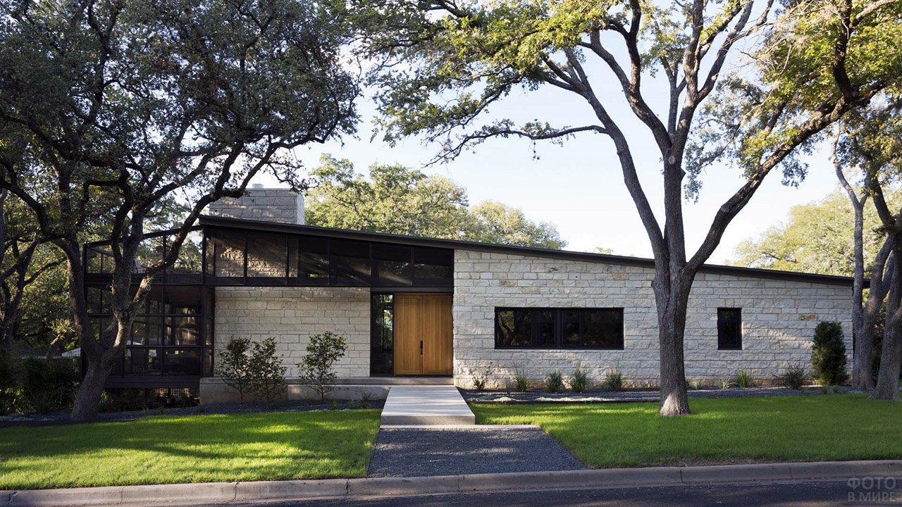 Кирпичный одноэтажный дом с односкатной крышей под тенистыми кронами деревьев