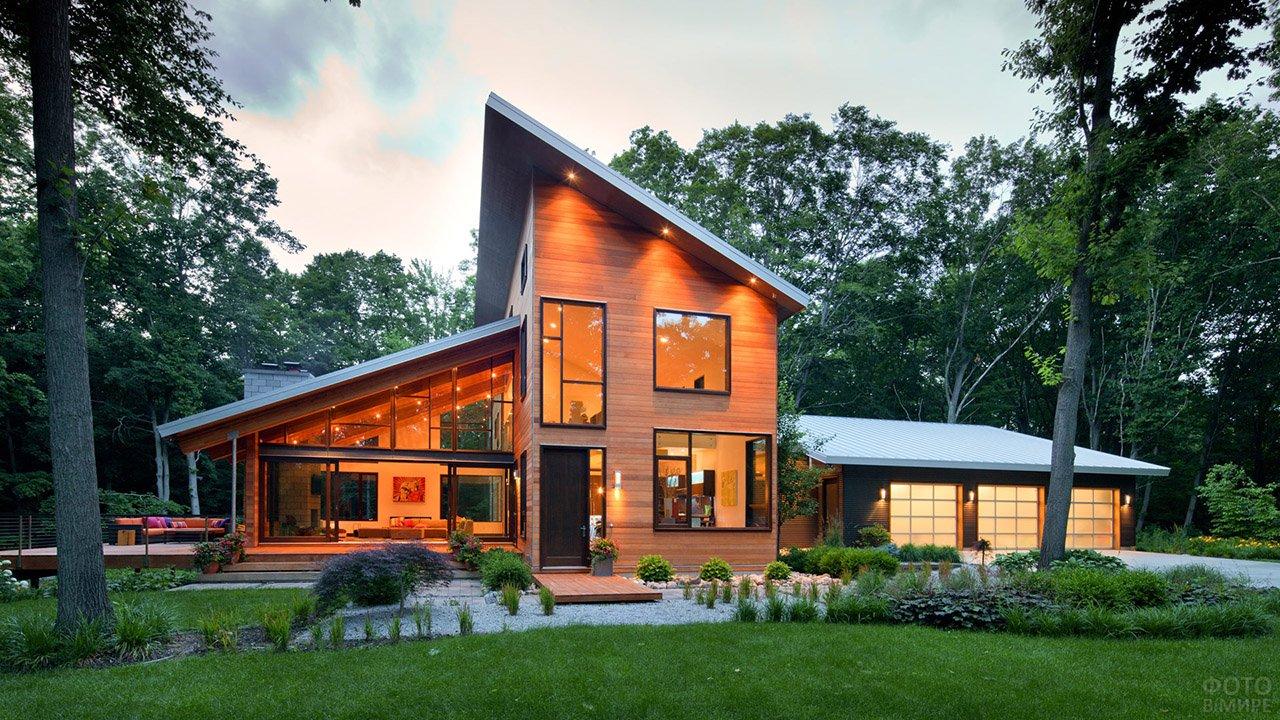 Комбинированная односкатная крыша просторного загородного дома на участке с деревьями