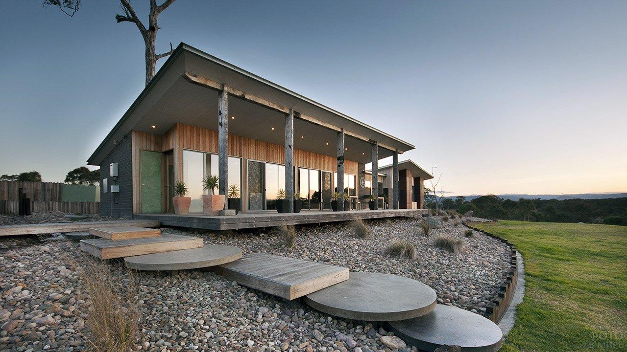 Модульный дом с верандой под односкатной крышей на деревянных колоннах с рокарием и лужайкой