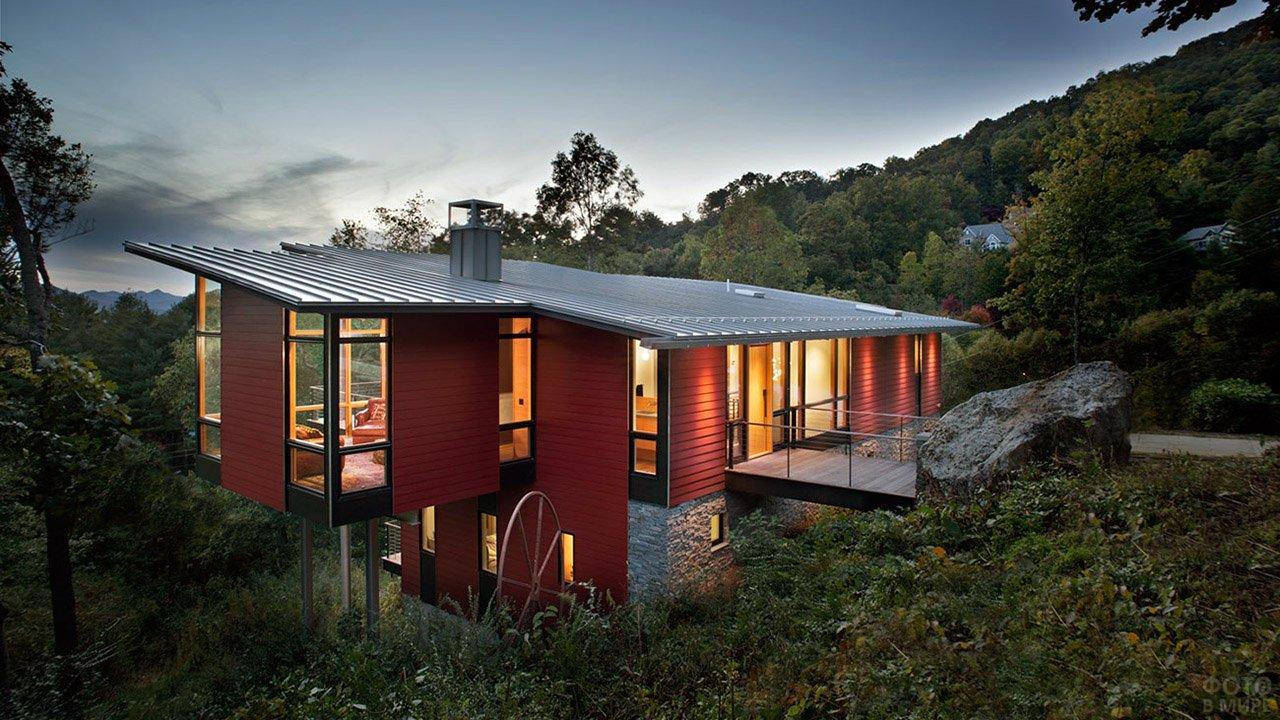Односкатная крыша красного дома на сваях на вечернем склоне холма