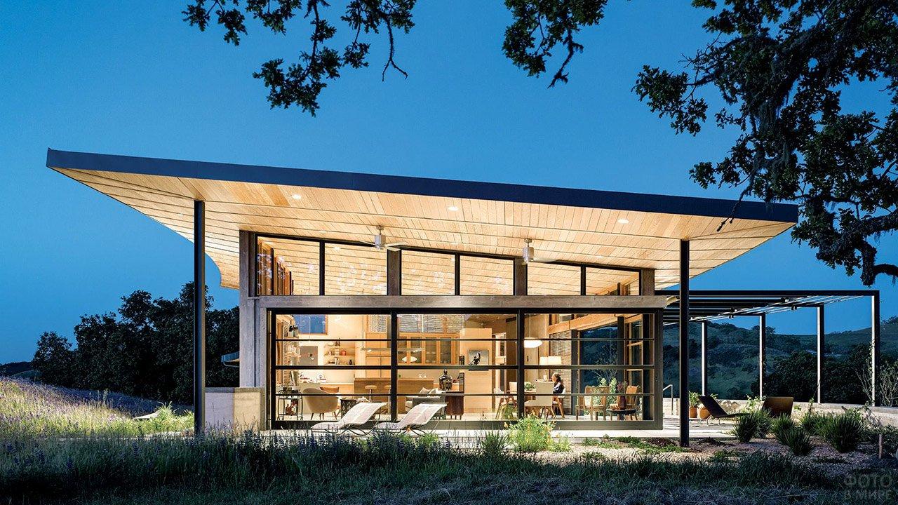 Пологая односкатная крыша современного загородного дома с вечерним освещением