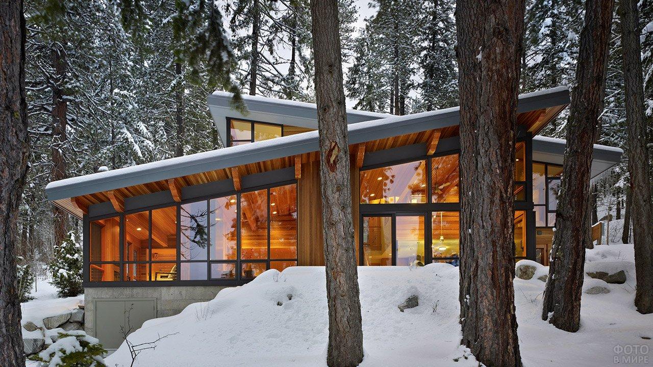 Шале с односкатной крышей в заснеженном лесу