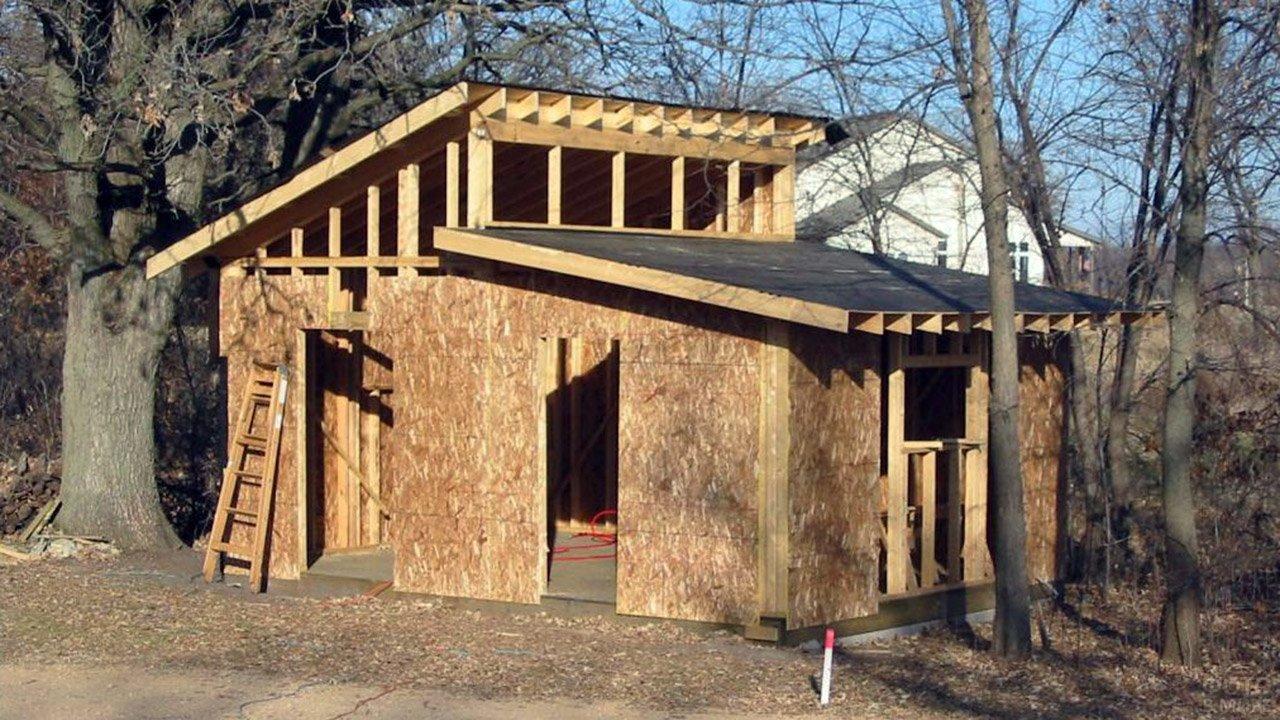 Строительство небольшого дома с комбинированной односкатной крышей под старыми деревьями