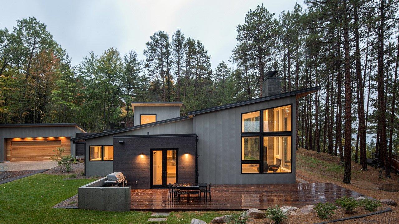 Типовой скандинавский дом у озера с односкатной крышей и верандой