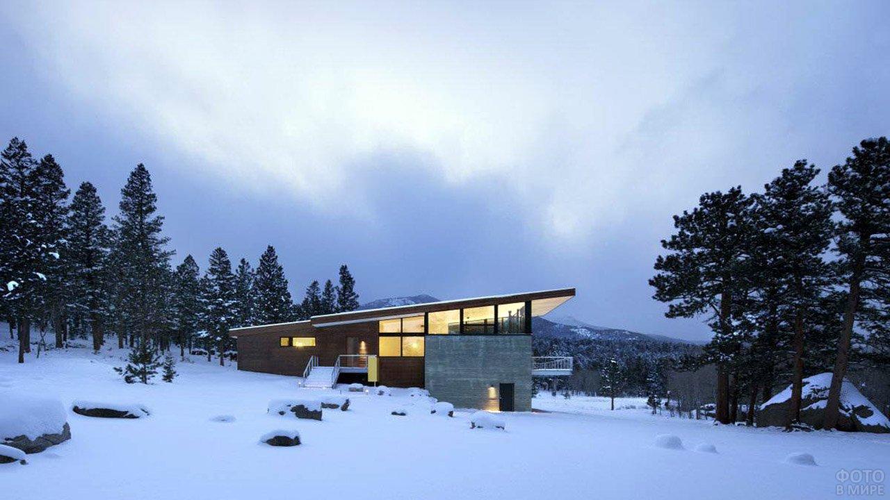 Загородный особняк с односкатной крышей в заснеженных вечерних горах