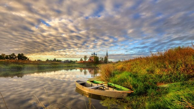 Лодки у берега и церковь за рекой
