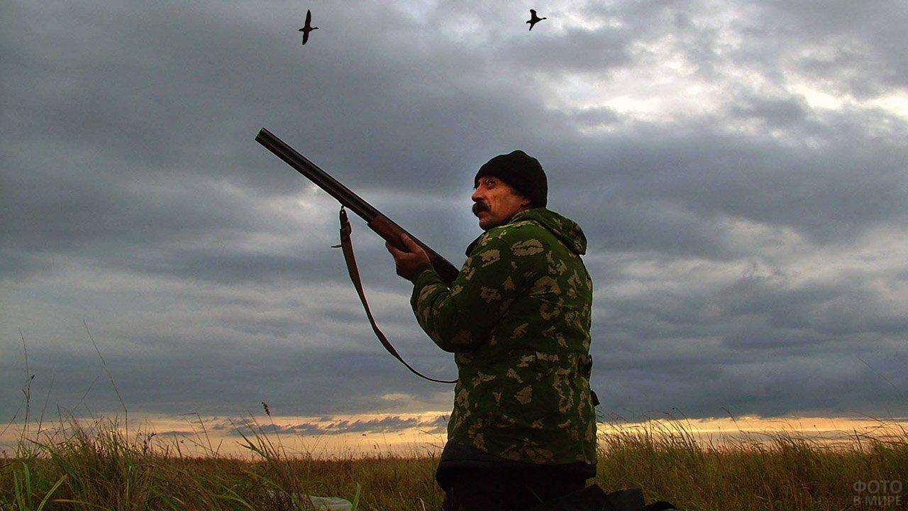 Мужчина с ружьём на осенней утиной охоте