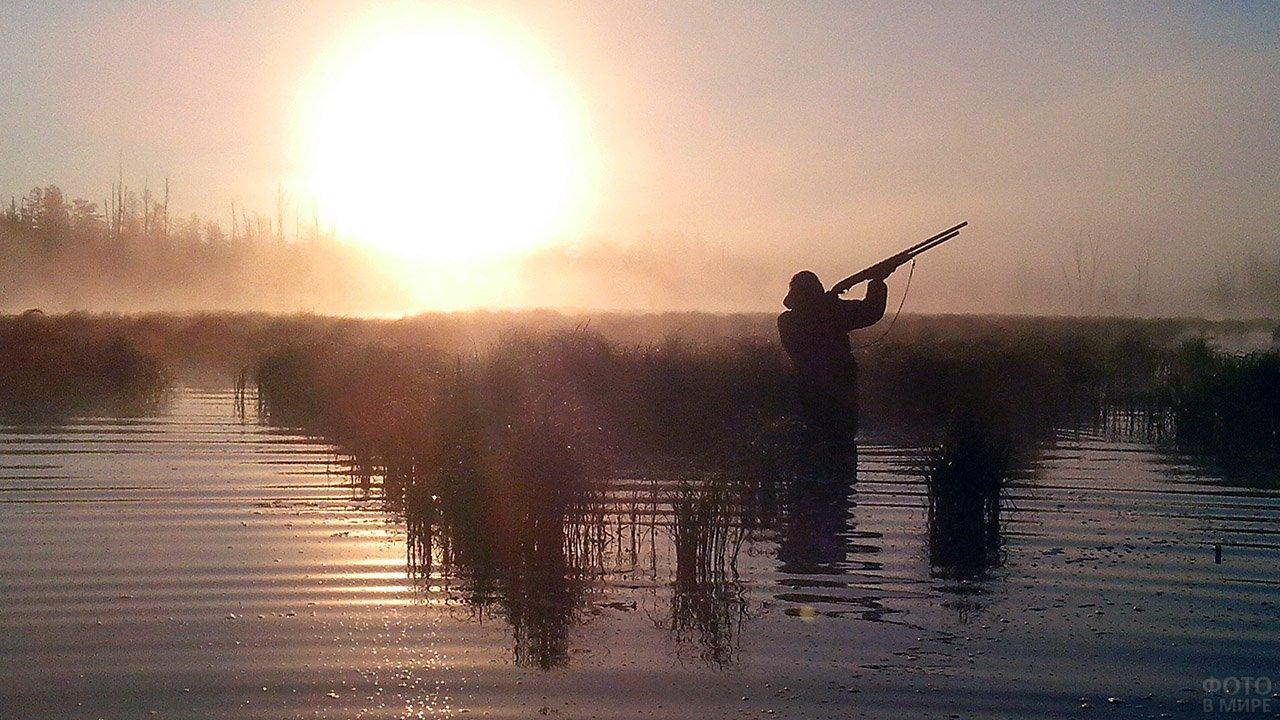 Силуэт охотника с ружьём на фоне рассвета над рекой