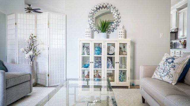 Белая гостиная с винтажной коллекцией в невысоком шкафу-витрине