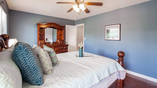 Бело-голубой интерьер спальни с акцентами из натурального дерева