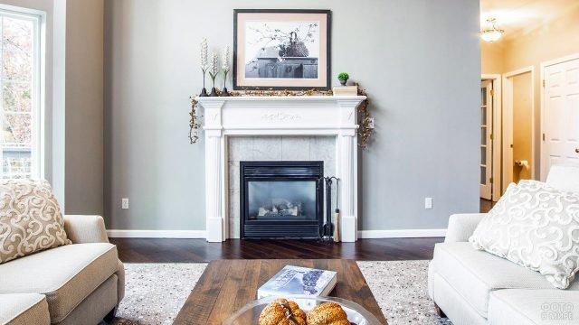 Белый классический камин на фоне трендово-серой стены в гостиной с деревянным полом