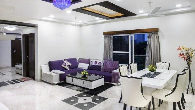 Фиолетовый текстиль в белой гостиной-столовой с чёрными акцентами