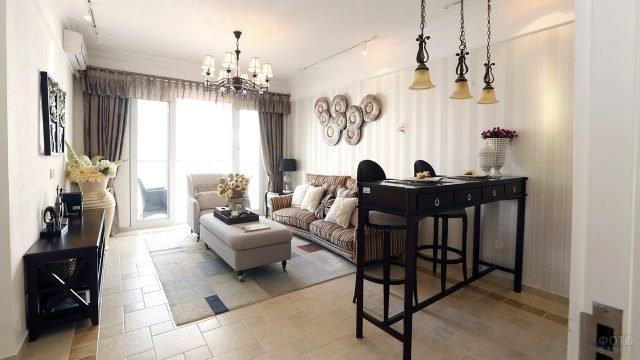 Классический интерьер гостиной с полосатым диваном и барным столом цвета венге