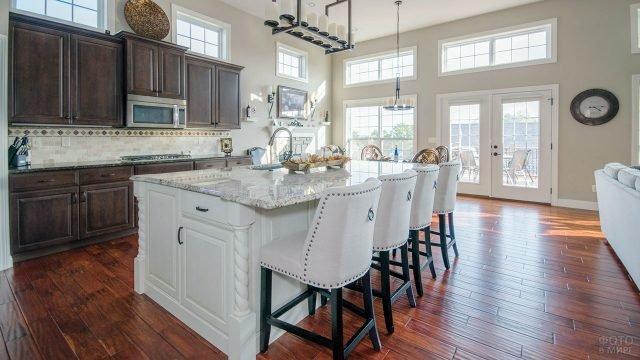 Просторная кухня-столовая с модным столом-островом в классическом стиле