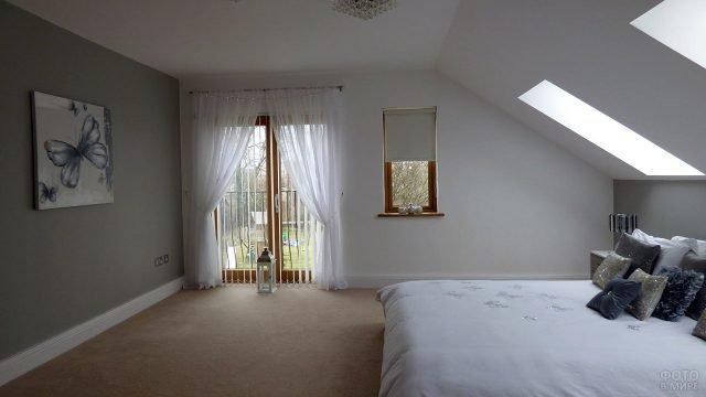 Спальня в мансарде с трендовой серой стеной и французским балконом