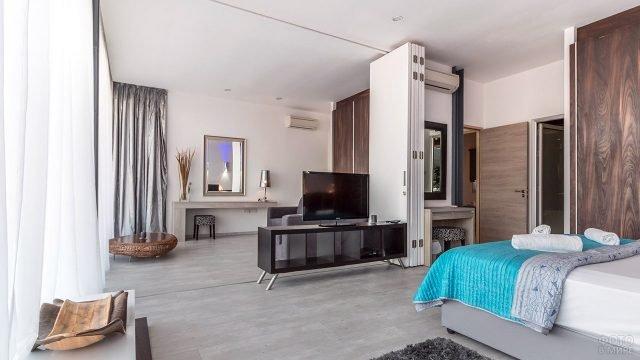 Стильная зонированная спальня с панелями из натурального дерева