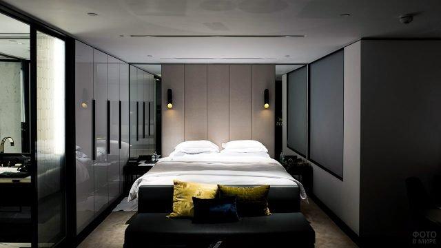 Стильный интерьер спальни цвета мокко со стеклянной дверью в ванную