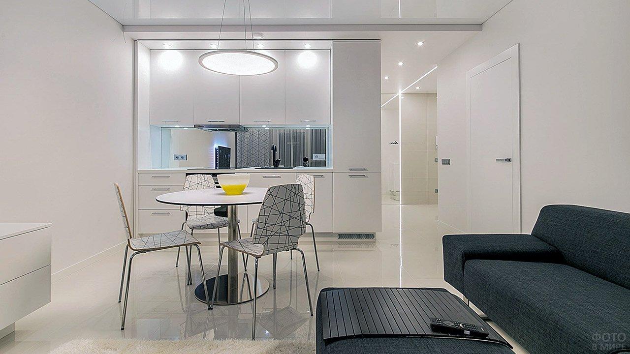 Студия с чёрной мебелью в гостиной и белой кухней-столовой