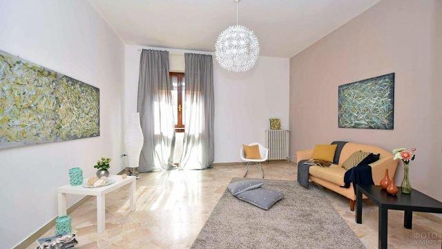 Светлая гостиная с контрастной мебелью у бежевой стены и современными картинами