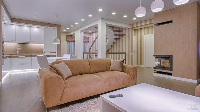 Зонированная двуцветная студия с кухней-гостиной и угловым камином напротив винтовой лестницы
