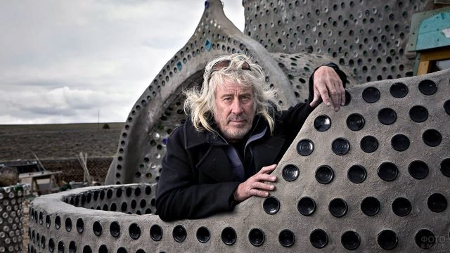 Архитектор на стене здания из бутылок своего авторства