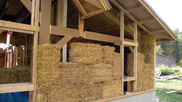 Балки каркаса и соломенные блоки в стене недостроенного дома