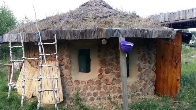 Дом из дров и глины на зелёном газоне