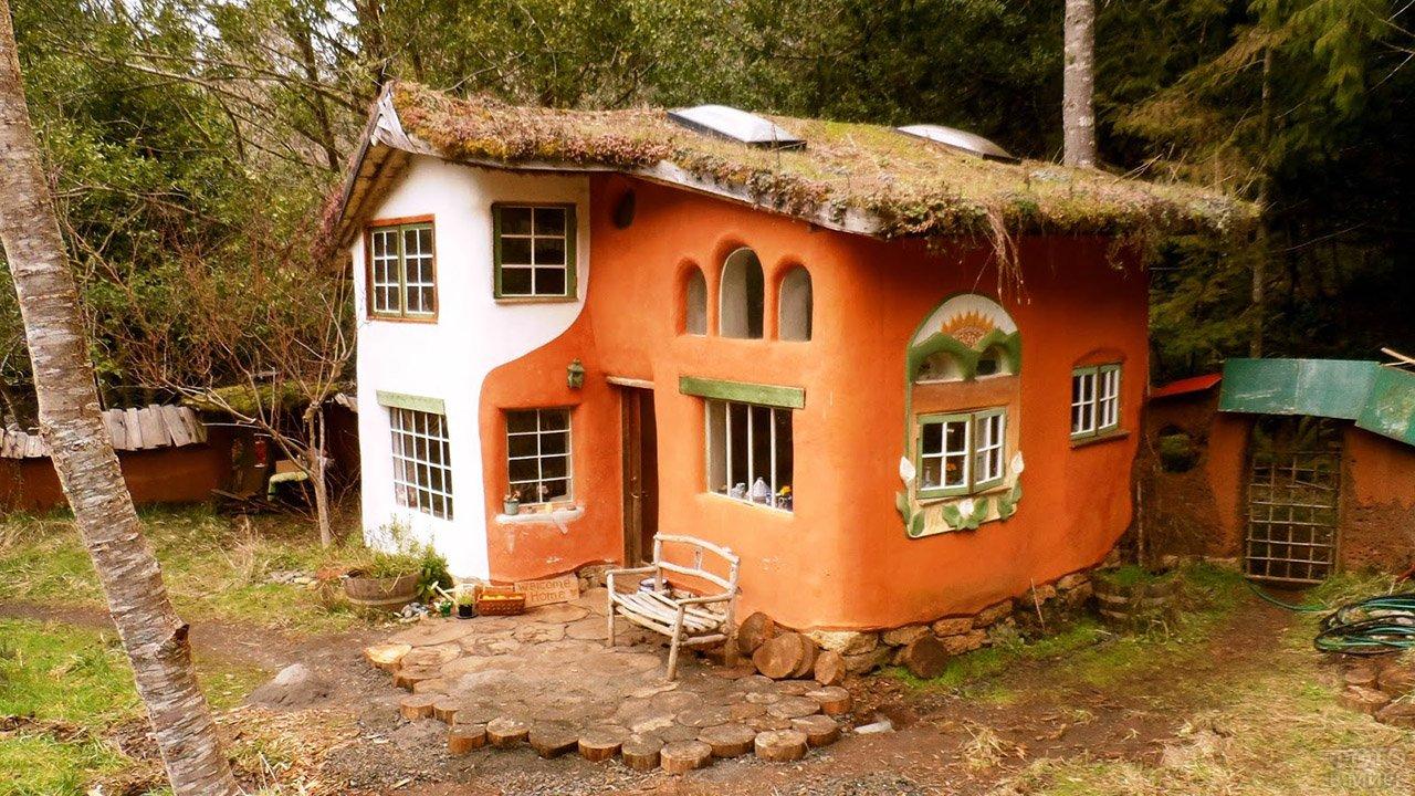 Домик из глины с двухцветными стенами и растущей на крыше травой