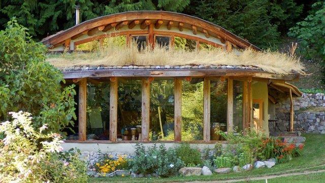 Красивый дом-землянка с колоннами на застеклённой веранде