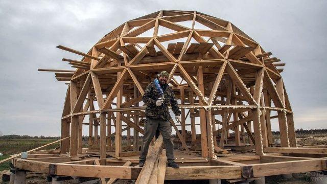 Мужчина строит каркас купольного дома