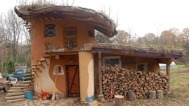 Паленница у глиняного дома в форме гриба с необычной крышей