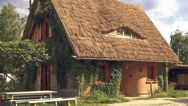 Увитый плющом дом из глины с соломенной крышей