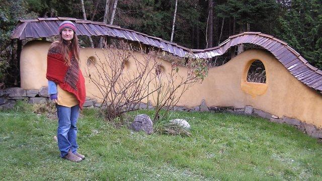 Женщина-хиппи рядом с лесным эко-домом из глины