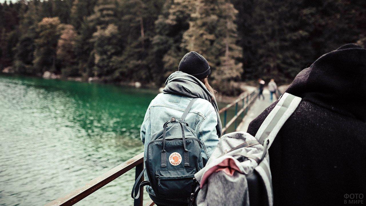 Девушка идёт с друзьями по мостику над лесной речкой