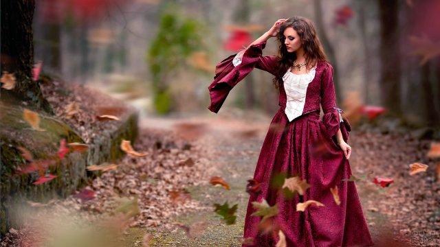 Модель в старинном наряде под листопадом в осеннем лесу