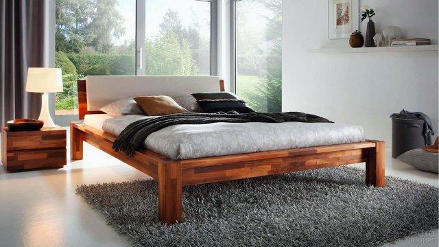 Деревянная двуспальная кровать из массива дерева в светлой современной спальне