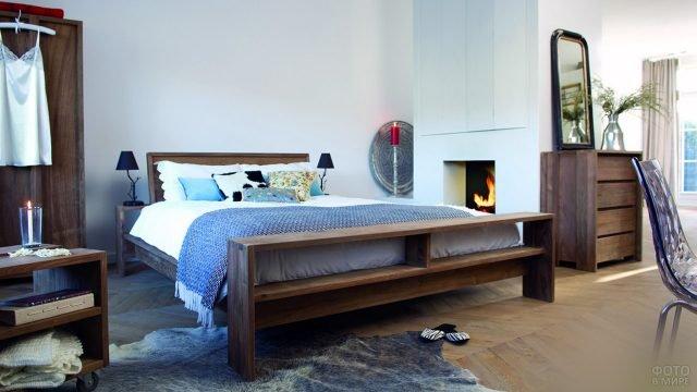 Деревянная кровать в колониальном стиле в современной спальне с камином
