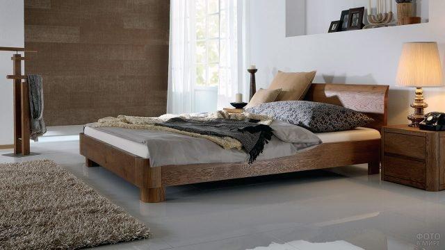 Двуспальная деревянная кровать с римским изголовьем в уютном интерьере