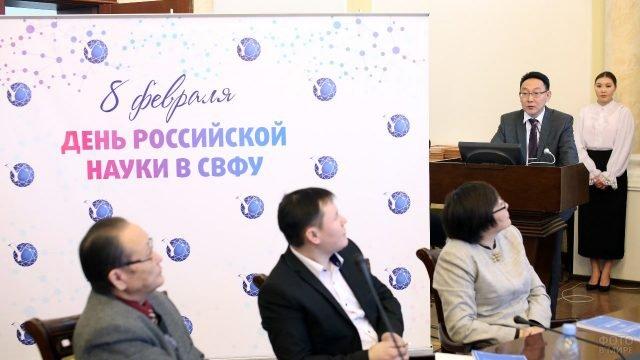 Докладчик на фоне баннера в День российской науки в Якутском ВУЗе