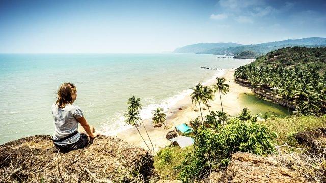 Девушка сидит на вершине холма над пляжем на Южном Гоа