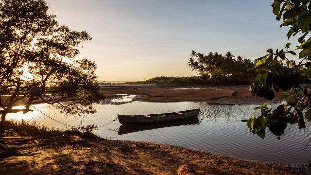 Рассвет над пляжем Гоа, лодка на мелководье впадающей в море реки