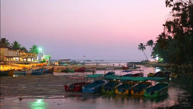 Сиреневый закат над пляжем с туристическими лодками на Гоа