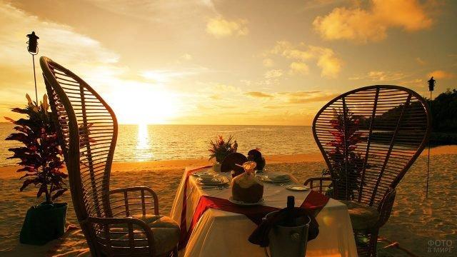 Столик на двоих на фоне заката над пляжем Гоа
