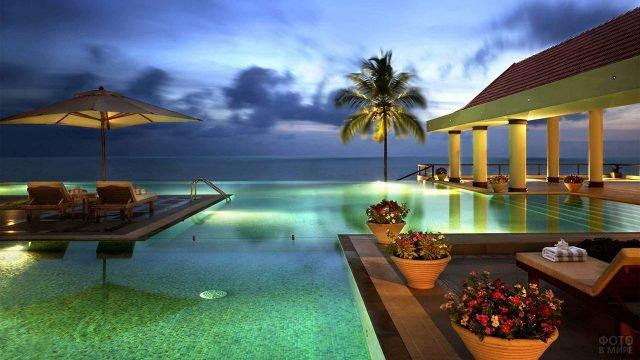 Вечернее освещение веранды с бассейном пятизвёздочного отеля на Гоа