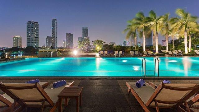 Ночные огни Бангкока с веранды спа-отеля с бассейном под пальмами