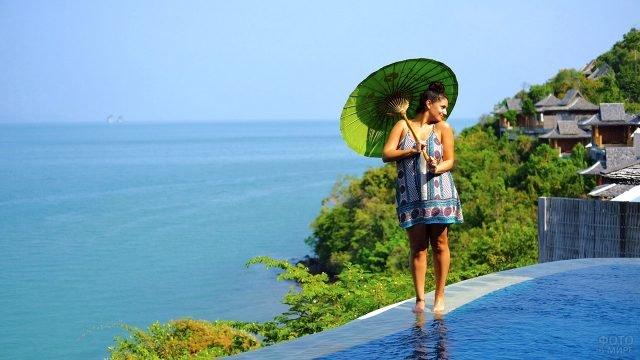 Туристка с зонтиком на краю бассейна при спа-отеле над пляжем Лох Паред