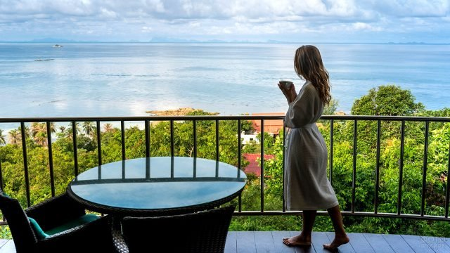 Туристка смотрит на горизонт с балкона отеля на острове Пханган